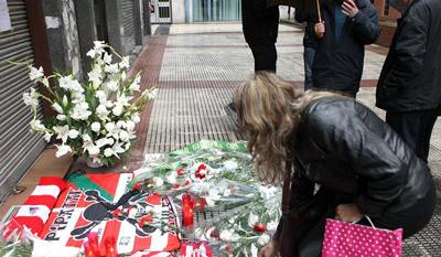 Una mujer deposita unas flores en el lugar en el que resultó herido Iñigo Cabacas, fallecido ayer. EFE