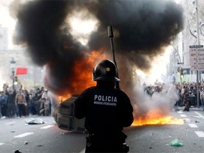Un policía ve como se quema un contenedor durante la huelga general en Barcelona. CARLOS RUANO / REUTERS