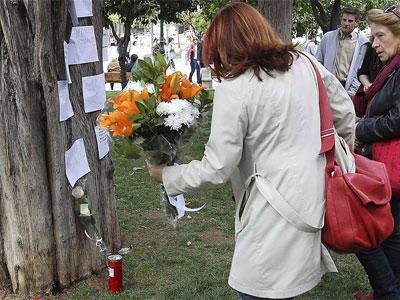 Una mujer deposita un ramo de flores en el lugar donde el anciano se suicidó de un disparo - EFE
