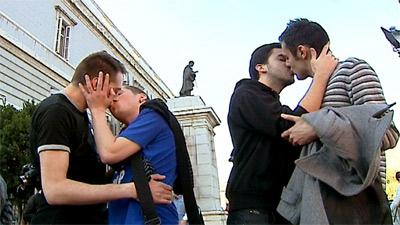 Cuatro jóvenes participan en la 'besada santa' a las puertas de la catedral de La Almudena de Madrid.-EFE