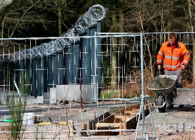 Un albañil trabaja en la construcción de una verja de seguridad. EFE/Archivo