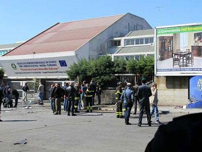 Varios bomberos y policías congregados delante del instituto profesional 'Morvillo Falcone' en la localidad italiana de Brindisi. EFE/Dario Caricato