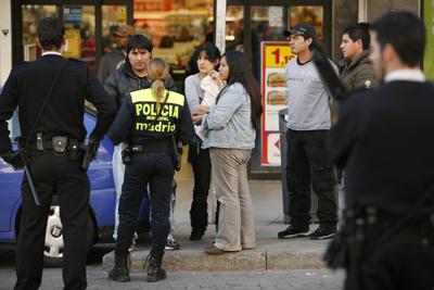 Una agente identifica a tres inmigrantes en el barrio de Lavapiés (Madrid). - EDU LEÓN