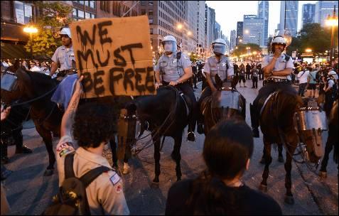 """Um manifestante segura um sinal dizendo 'Nós temos que ser livre """"enquanto protestavam contra a cimeira da NATO nas ruas de Chicago (EUA).  EPA / Tannen MAURY"""