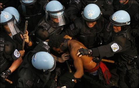 Polícia prende um manifestante durante um protesto contra a cimeira da NATO em Chicago (EUA).  Manifestantes e policiais encenaram episódios de violência no final de uma marcha pela paz, quando parte da multidão se recusou a se dispersar, apesar dos pedidos de aplicação da lei.  EPA / JOHN SMIERCIAK