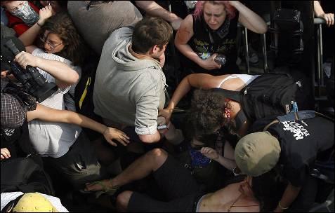 Polícia empurrar os manifestantes atrás das grades durante um protesto contra a cimeira da NATO em Chicago (EUA).  Manifestantes e policiais encenaram episódios de violência no final de uma marcha pela paz, quando parte da multidão se recusou a se dispersar, apesar dos pedidos de aplicação da lei.  EPA / JOHN SMIERCIAK