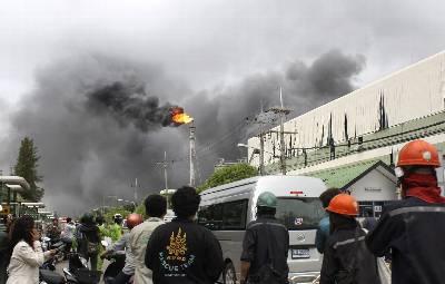 Fotografía facilitada hoy de trabajadores de una fábrica observan el fuego causado por una explosión en en una fábrica petroquímica situada Map Ta Phut al sur de Tailandia.