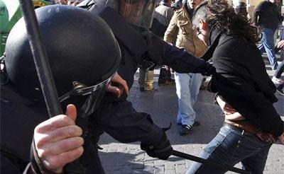 Una joven es golpeada por la policía durante las protestas de los estudiantes valencianos contra los recortes en educación.- AP