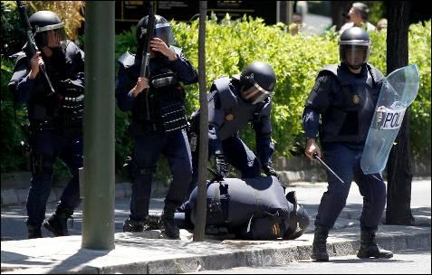 Un policía herido en posición de defensa, mientras es protegido por otros agentes - EFE