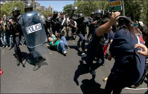 Varios manifestantes tratan de escapar en una de las cargas policiales en la Castellana - EFE