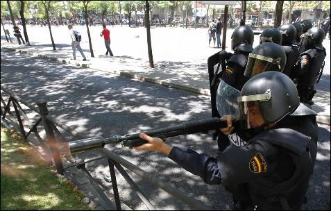Un agente de la policía antidisturbios dispara una pelota de goma a los manifestantes - AFP