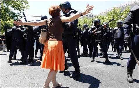 Una manifestante se acerca a los antidisturbios y discute con un agente - AFP