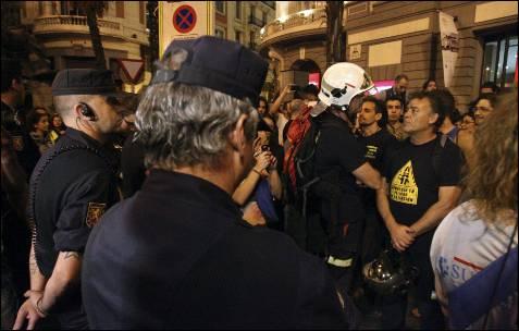 Varios de los funcionarios, entre ellos policías, bomberos o profesores, vigilados por miembros de la policia nacional, durante la manifestación que ha recorrido esta tarde-noche distintas zonas de la capital madrileña. EFE/Victor Lerena