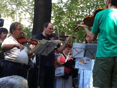 La 'Orquesta Solfónica', la banda del 15-M, interpreta música clásida en el Paseo del Prado - Foto: @letras15M