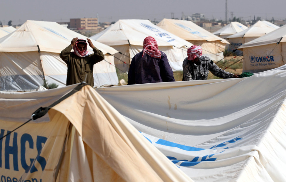 Trabajadores caminan entre las tiendas de campaña en el Camp Zaatari, el primer campamento oficial de refugiados de Jordania. AFP PHOTO / KHALIL MAZRAAWI