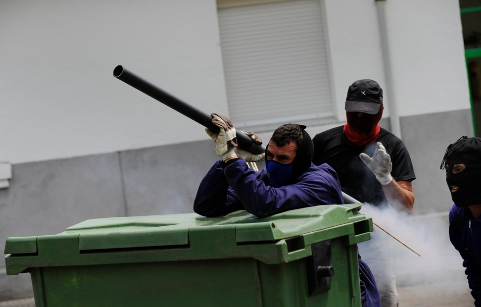 Un grupo de mineros lanza un cohete en las calles de Ciñera - REUTERS