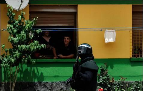 Dos vecinos observan a un guardia civil antidisturbios - REUTERS