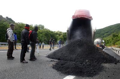 Los mineros descargan un camión con carbón procedente del extranjero en la A-6, este viernes.- Ana F. Barredo