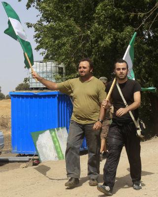 Los dos miembros del Sindicato Andaluz de Trabajadores (SAT), Andrés Amoro (2i) y Francisco Molero (d) llegan a la finca 'Las Turquillas' de Osuna (Sevilla), ocupada por los jornaleros desde hace 17 días. EFE/Juan Ferreras