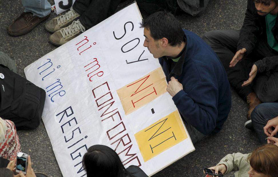 Un manifestante se sienta con una pancarta en la madrileña plaza de Neptuno, durante la manifestación convocada por la Coordinadora 25S dentro de la iniciativa 'Rodea el Congreso'. EFE/Ángel Díaz