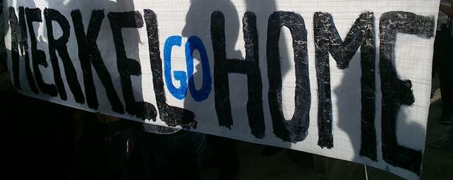 Una de las pancartas que se han podido ver hoy durante el recibimiento indignado a la canciller alemana - E. M.