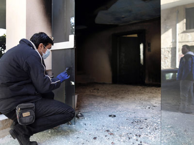 Un policía examina los daños a un edificio atacado con bombas incendiarias el pasado domingo en Atenas.