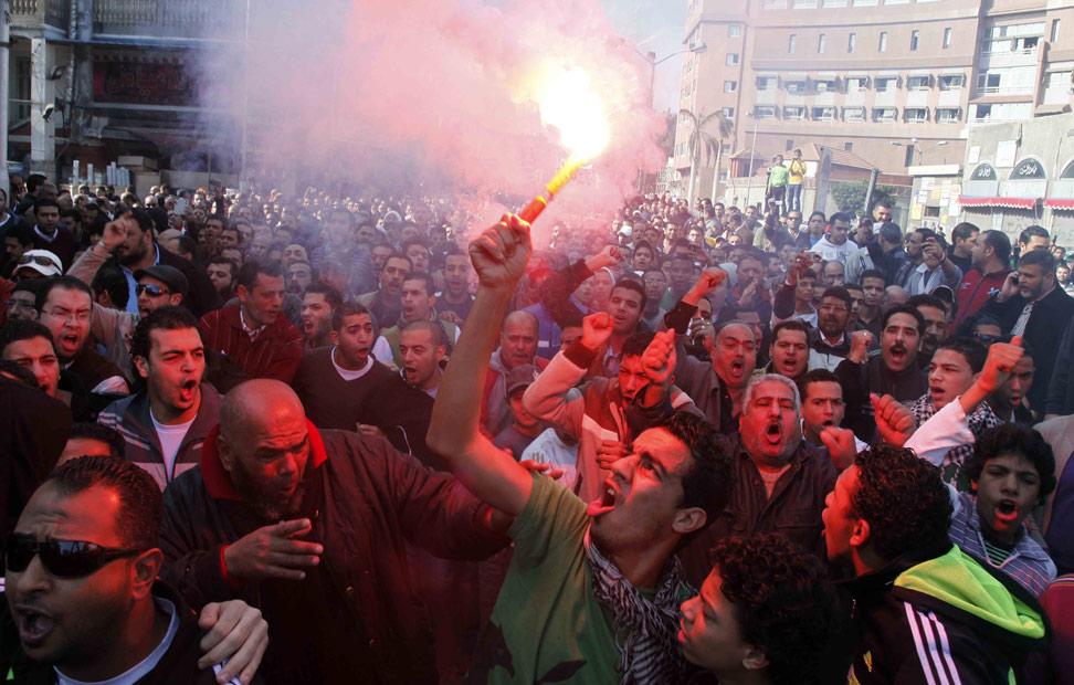 Un manifestante egipcio y seguidor de al-Masry Club de fútbol, sujeta una vengala durante una manifestación frente a la cárcel de la ciudad egipcia del canal Suez,Port Said, el pasado 25 de enero.