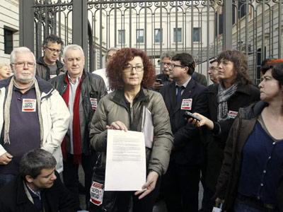 La madre de Alfonso Fernández, Elena Ortega, a las puertas del Congreso de los Diputados. Tra ella, diputados de la izquierda parlamentaria.