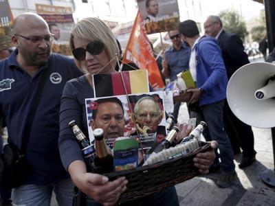 Una manifestante lleva una cesta con los retratos del ministro griego de Finanzas, izq), y de su homólogo alemán, junto con bebida y comida, a las puertas del Ministerio de Finanzas en Atenas, 17 de octubre de 2013. EFE/Alkis Konstantinidis