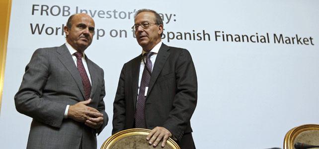 El ministro de Economía, Luis de Guindos, acompañado por el director general del Fondo de Reestructuración Ordenada Bancaria (FROB), Antonio Carrascosa.