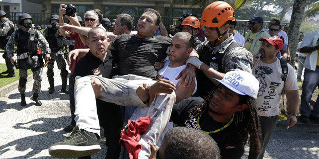 Los manifestantes portan a un herido de durante un enfrentamiento con los soldados de la Fuerza Nacional de Barra da Tijuca playa cerca del Hotel Windsor.-