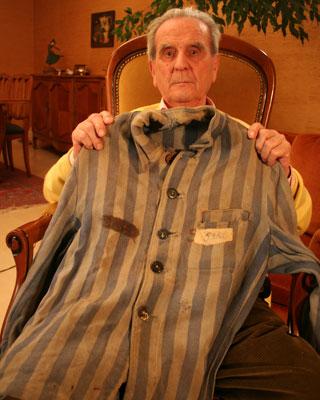 El deportado Eduardo Escot (Olvera, Cádiz, 1919) con la chaqueta a rayas que llevó en Mauthausen, en su domicilio en Rosny sous Bois, cerca de París.