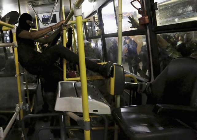 Uno de los manifestantes golpeando un autobús. REUTERS