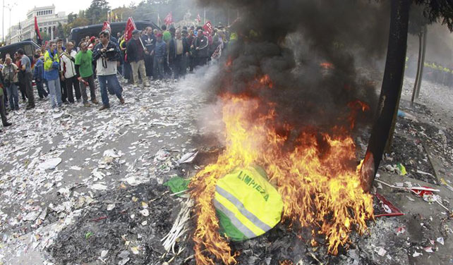 Los trabajadores de limpieza viaria y jardinería de Madrid queman sus uniformes frente al Ayuntamiento en protesta por los 1.144 despidos anunciados.