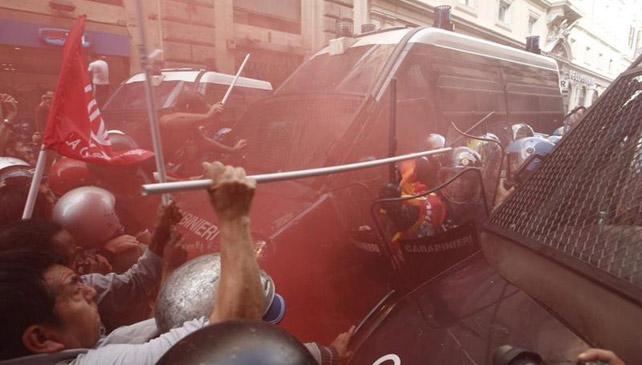 Activistas por el derecho a la vivienda se enfrentan a los caravinieros en el centro de Roma.