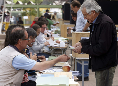 Un chileno recoge las papeletas para votar en una mesa electoral hoy, domingo 17 de noviembre.- Felipe Trueba (EFE)