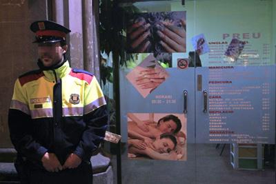 Un agente de los Mossos d'Esquadra durante la redada efectuada en una peluquería de origen chino de la capital catalana.- Toni Albir(EFE)