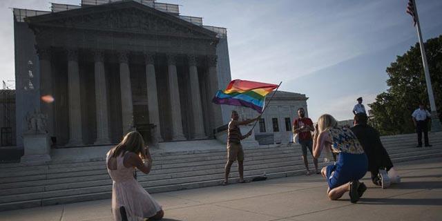 Un hombre ondea una bandera ante la corte del Tribunal Supremo de EEUU.- REUTERS