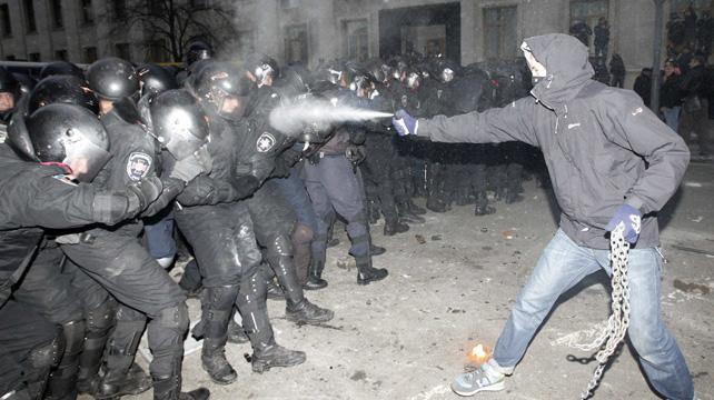 Una manifestantes rocía con un spray a agentes antidisturbios en Kiev.