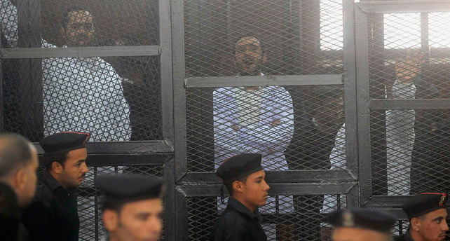 Los activistas políticos Ahmed Maher (d), Ahmed Douma (c) y Mohamed Adel, del Movimiento 6 de Abril, miran desde detrás de las rejas en la corte Abdeen, en El Cairo