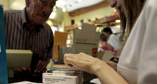 Un jubilado acude a la farmacia a comprar medicamentos.