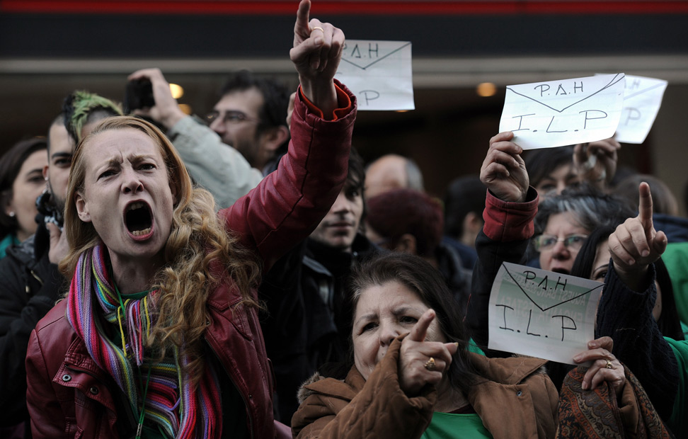 Activistas antidesahucios protestan mostrando dibujos de sobres frente a la sede del Partido Popular en Barcelona.