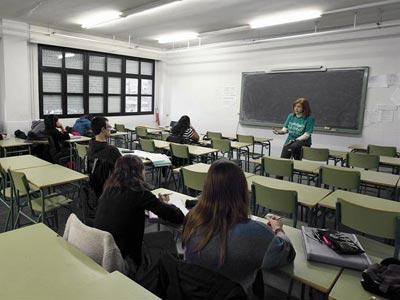 Una profesora imparte clase en aula prácticamente vacía, en el instituro Juan de la Cierva de Madrid. EFE/ Ángel Díaz