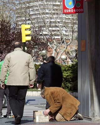 Un hombre pide limosna a la puertas de una entidad bancaria en Zaragoza.