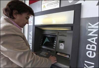 Una mujer saca dinero ayer de un cajero automático en Nicosia, Chipre.