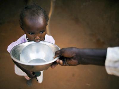 La joven Ismael Adam bebe agua de un cuenco en el refugio para desplazados de Abu Shouk en Darfur (Sudán). EFE/ Unamid Handout/Albert Gonzalez