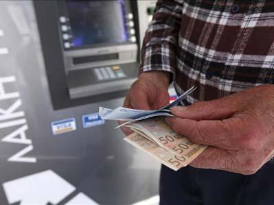 Un hombre saca dinero de un cajero.
