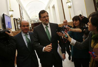 El presidente del Gobierno, Mariano Rajoy, con el ministro de Economía, Luis de Guindos, en los pasillos del Congreso de los Diputados.