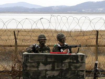 Soldados surcoreanos vigilan tras una barricada cerca del río Imjin cerca de la zona desmilitarizada en Paju. Al fondo, Corea del Norte. EFE