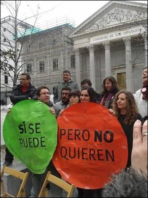 Miembreos de la PAH y la Asamblea de Vivienda de Madrid posan con los nuevos carteles para su campaña ante el Congreso de los Diputados.